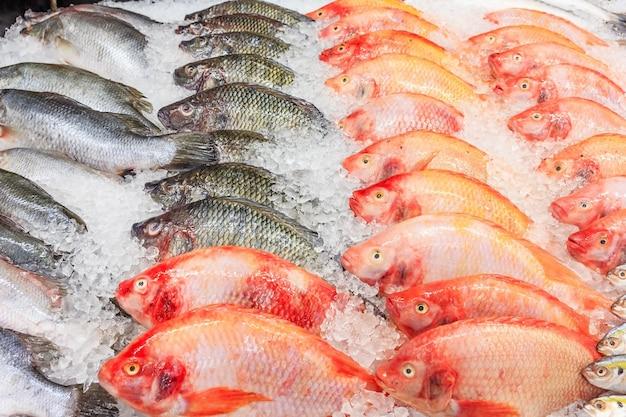 Gefrorener nil tilapia fish in einem stapel des eises am supermarkt, mischfisch für verkauf auf einem markt