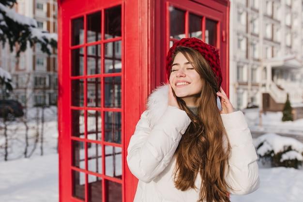 Gefrorener sonniger schneemorgen der fröhlichen jungen frau mit dem langen brünetten haar im roten hut, der winterzeit nahe roter telefonzelle auf der straße genießt. chillen auf der sonne, lächelnd mit geschlossenen augen.