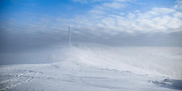 Gefrorener zellularer turm. gefrorene telekommunikationstürme mit teller und mobilfunkantenne gegen blauen himmel in den winterbergen.