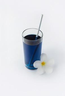 Gefrorenes blaues schmetterlingserbsengetränk mit tropischem blumendekor. gesunder thailändischer traditioneller cocktail im glas. sommer erfrischendes getränk