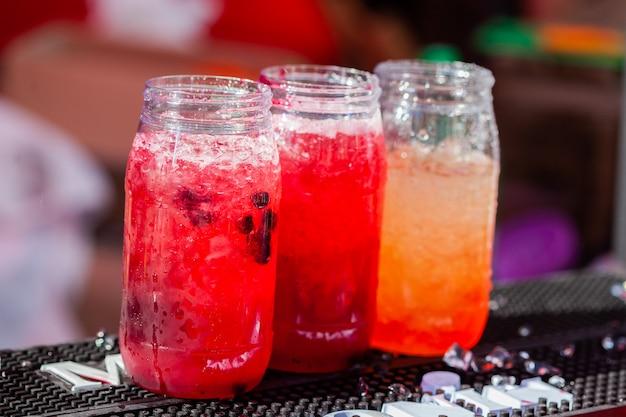 Gefrorenes cocktail mit orange und wassermelone auf dem holztisch im freien