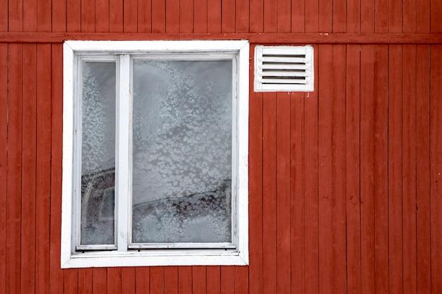 Gefrorenes fenster in einem alten, rot gestrichenen verlassenen gebäude in pyramiden im spitzbergen-archipel.