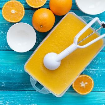 Gefrorenes fruchtpüreesorbet in einer großen schüssel auf blauem holzhintergrund wird mit keilen von reifem orange verziert