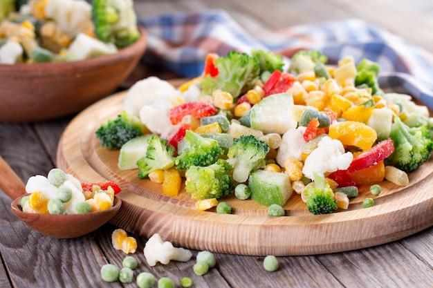 Gefrorenes gemüse auf holzbrett auf tisch