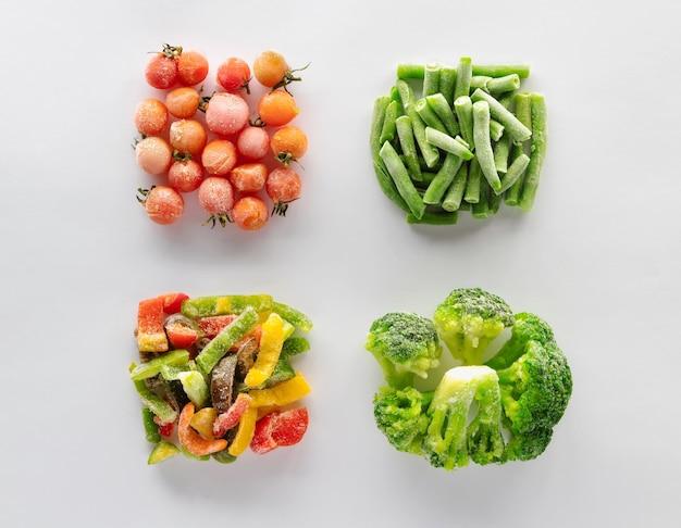 Gefrorenes gemüse auf weißem hintergrund. kirschtomaten, grüne bohnen, paprika und brokkoli werden in quadraten ausgelegt.