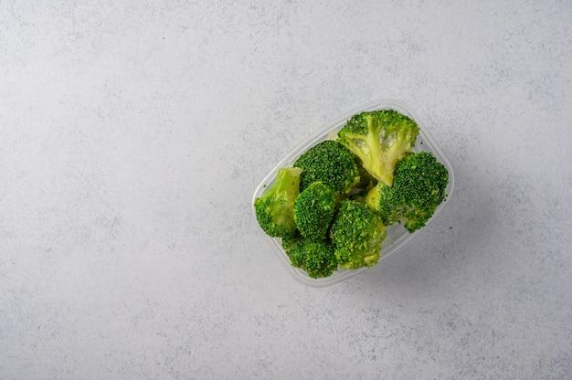 Gefrorenes gemüse brokkoli in einer plastikschale auf einer grauen oberfläche konzeptdiäten und gesunde ernährung