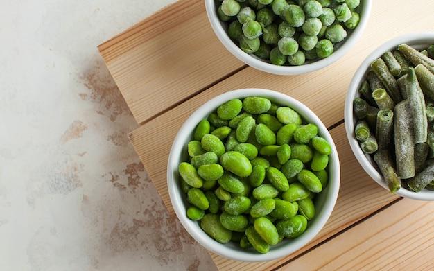 Gefrorenes gemüse, grüne erbsen, soja, grüne bohnen und babynahrung in weißen schalen