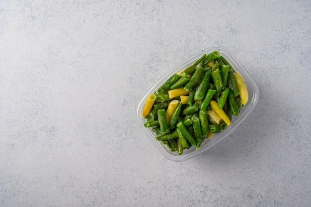 Gefrorenes gemüse grüne hülsen bohnen in plastikschale auf einer grauen oberfläche konzeptdiäten und gesund