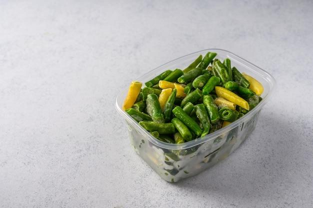Gefrorenes gemüse grüne hülsenbohnen in der kunststoffschale auf einem konzept des selektiven fokus der grauen oberfläche