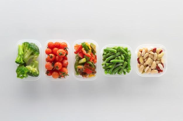 Gefrorenes gemüse in plastikbehältern auf weißem hintergrund. gefrorener brokkoli, grüne bohnen, kirschtomaten, bohnen und paprika.