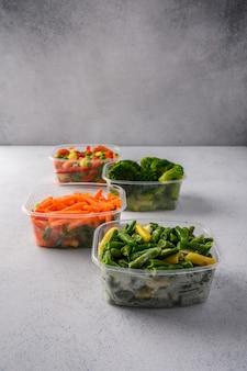 Gefrorenes gemüse karottenbrokkoli spinat grüne schoten bohnen in plastikschalen auf grauer oberfläche