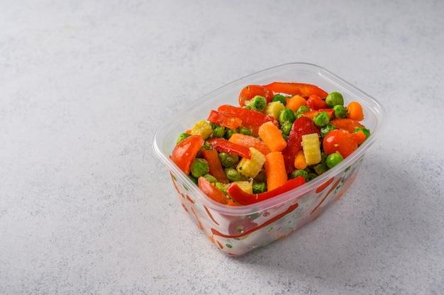 Gefrorenes gemüse mais paprika erbsen karotten tomaten in plastikschale auf einer grauen oberfläche