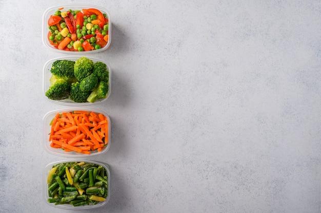 Gefrorenes gemüse mischt grüne bohnen aus karottenbrokkoli-spinat in plastikschalen auf einer hellen oberfläche