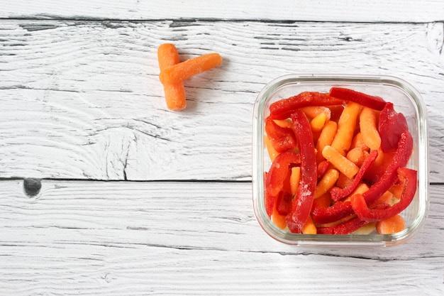 Gefrorenes gemüse wie rote paprika und babykarotte in transparenten schalen auf der rechten seite