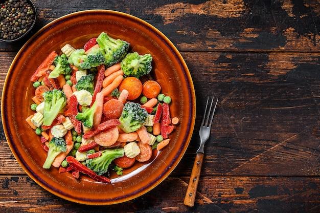 Gefrorenes geschnittenes gemüse, brokkoli, paprika, tomaten, karotten, erbsen und mais auf einem teller. dunkel