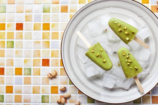 Gefrorenes hausgemachtes pistazieneis am stiel in einer schüssel mit eis auf dem mosaikfliesentisch erfrischendes eis am stiel gefrorener grüner saft auf dem kopienraum mit draufsicht