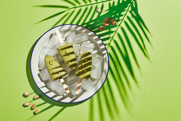 Gefrorenes hausgemachtes pistazieneis am stiel in einer schüssel mit eis auf grünem hintergrund mit palmblattschatten