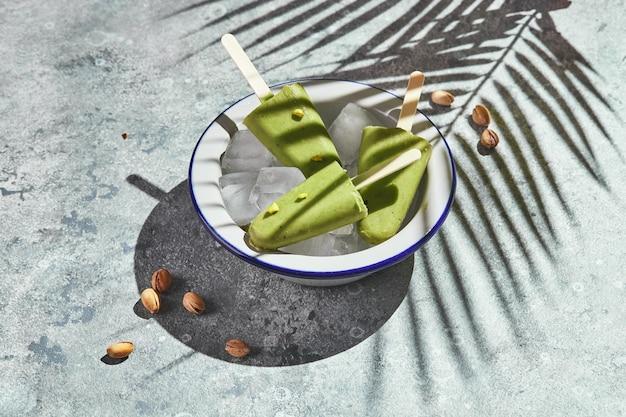 Gefrorenes hausgemachtes pistazieneis am stiel in einer schüssel mit eis