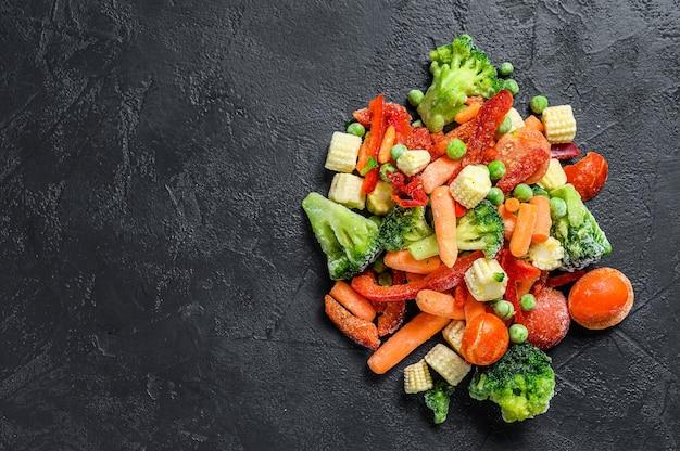 Gefrorenes kalt geschnittenes gemüse, brokkoli, paprika, tomaten, karotten, erbsen und mais. draufsicht.