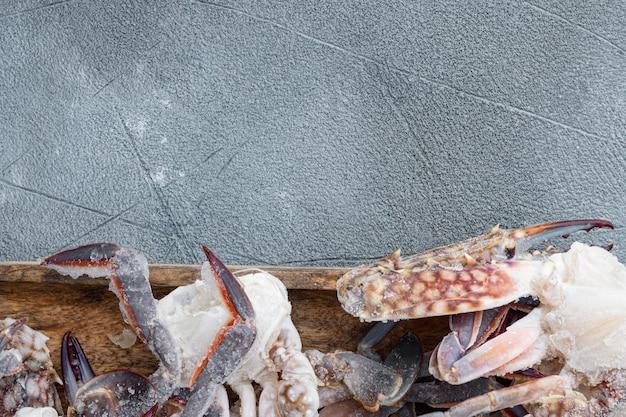 Gefrorenes rohes blaues schwimmkrabbenfleischset, auf holztablett, auf grauem tisch, draufsicht flach gelegt