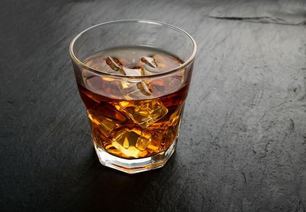 Gefrorenes whisky-glas auf natürlichem schwarzem steinhintergrund