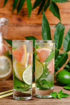 Gefrorenes zitrusgetränk mit soda, zitrusfrüchten und minze auf holztisch.