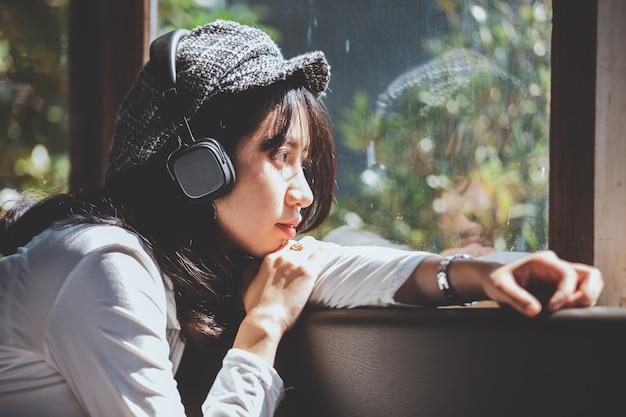 Gefühl, das dem jungen mädchen traurig ist, musik hörend, die heraus das fenster schaut
