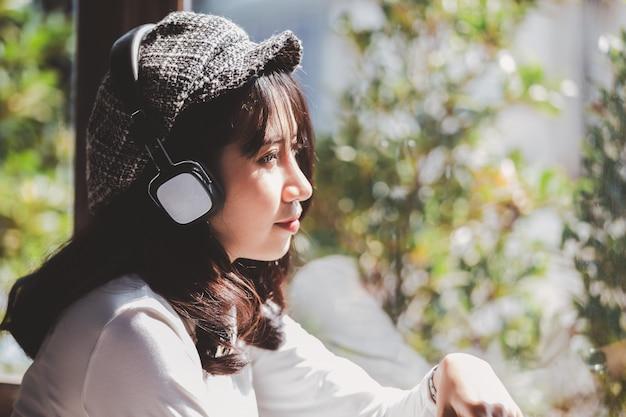 Gefühl, das trauriges hören des jungen mädchens zur musik schauend das fenster glaubt
