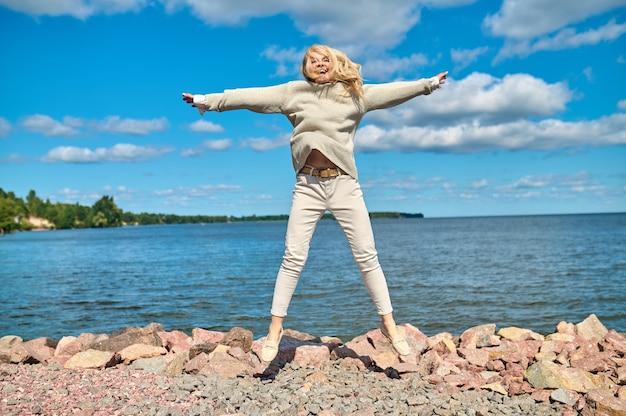 Gefühl der freiheit. energiegeladene lachende frau mit armen an den seiten beim springen an der küste an einem sonnigen warmen tag
