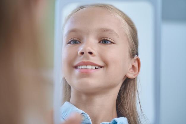 Gefühl der freiheit. fröhliches glänzendes gesicht eines süßen langhaarigen grundschulmädchens, das sich im innenspiegel glücklich ansieht