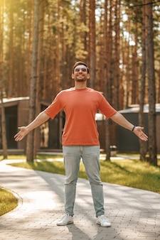 Gefühl der freiheit. zuversichtlich lächelnder gutaussehender mann mit sonnenbrille, der mit den händen zu den seiten unter der sonne im park steht