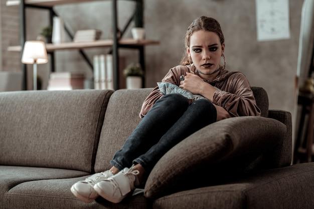 Gefühl schrecklich. dunkelhaariges teenager-mädchen, das auf dem sofa sitzt und sich schrecklich fühlt und nach problemen in der schule in tränen ausbricht?