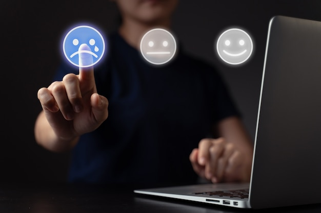 Gefühle der frau mit laptop- und emoticon-hologramm-effekt