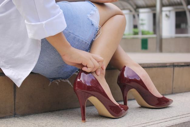 Gefühlsschmerz der jungen frau der nahaufnahme in ihrem fuß auf treppe, haben knöchelschmerz, gesundheitskonzept