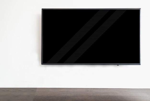 Geführtes intelligentes fernsehen, das am weißen wandhintergrund, mit hölzerner tabelle hängt.