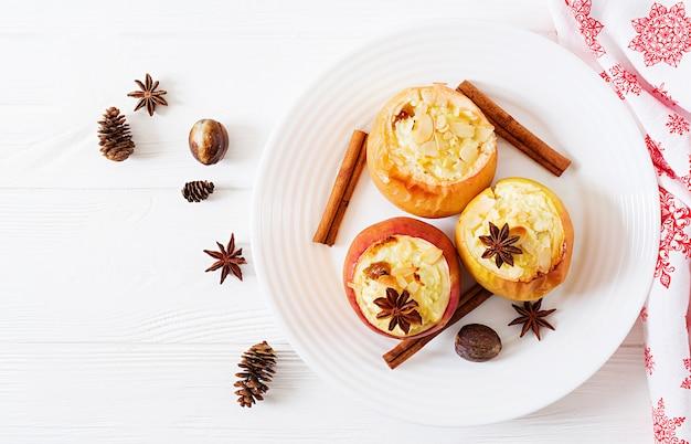 Gefüllte bratäpfel mit hüttenkäse, rosinen und mandeln zu weihnachten auf einem weißen hintergrund.