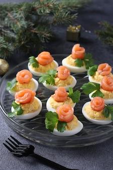 Gefüllte eier mit gesalzenem lachs und käse, ein köstlicher festlicher snack auf dunklem hintergrund.
