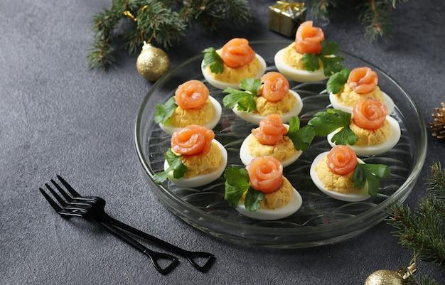 Gefüllte eier mit gesalzenem lachs und käse. leckerer festlicher snack auf dunklem hintergrund