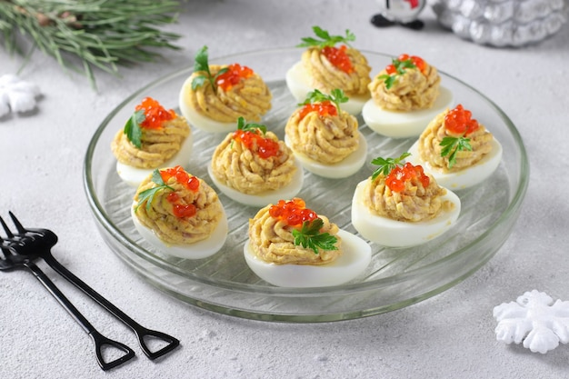 Gefüllte eier mit thunfisch und käse dekorierten roten kaviar, festlicher snack auf hellgrauem hintergrund.