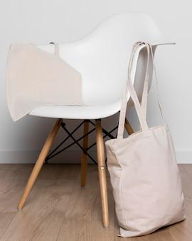 Gefüllte einkaufstasche und weißer stuhl