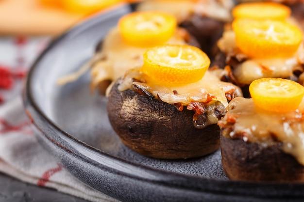 Gefüllte gebratene champignons mit käse, kumquats und erbsen. seitenansicht, nahaufnahme, makro.