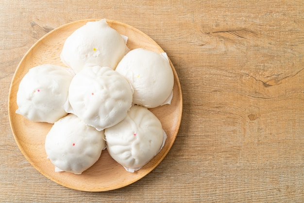 Gefüllte gedämpfte brötchen auf holzplatte - chinesisches essen
