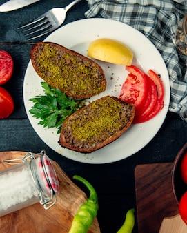 Gefüllte, halb geschnittene fleischwürfel, serviert mit zitrone und tomate