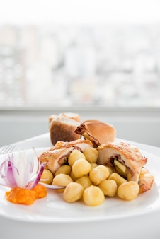 Gefüllte hühnerbrust mit gnocchi auf weißer platte