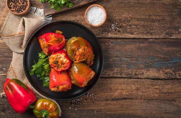 Gefüllte paprika mit fleisch, reis und gemüse auf holzhintergrund. ansicht von oben, kopienraum.