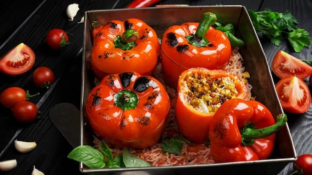 Gefüllte paprika mit reis, zwiebeln auf schwarzem steinhintergrund. ansicht von oben, flach