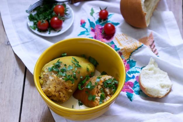 Gefüllte paprika serviert mit saurer sahne und brot