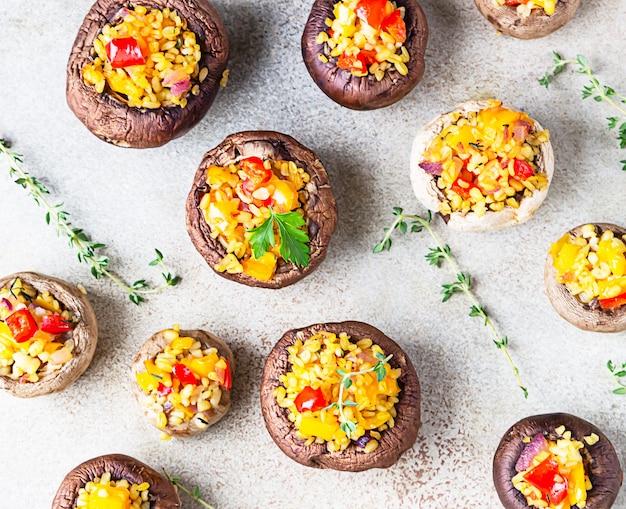 Gefüllte portobello-pilze mit bulgur, gemüse und aromatischen kräutern. vegetarisches essen.