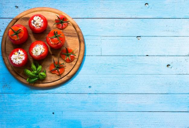 Gefüllte tomaten mit käse und verschiedenem gemüse auf holzuntergrund,