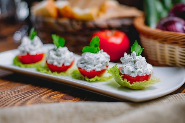 Gefüllte tomatenscheiben von der seite mit frischkäse und kräutern